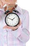 Mujer con un reloj de alarma en una mano. Imagen de archivo libre de regalías