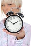 Mujer con un reloj de alarma en una mano. Fotografía de archivo libre de regalías