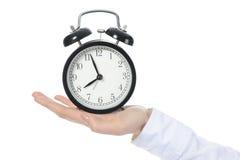 Mujer con un reloj de alarma en una mano. Fotografía de archivo