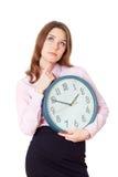 Mujer con un reloj en su pensamiento de las manos Imagen de archivo