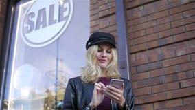 Mujer con un smartphone en la venta del letrero almacen de metraje de vídeo