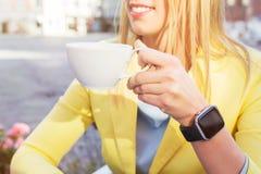 Mujer con un smartwatch alrededor de su muñeca que sostiene una taza de café Imágenes de archivo libres de regalías