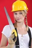 Mujer con un sombrero duro y un handsaw Imagen de archivo