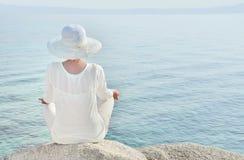 Mujer con un sombrero que hace frente a meditar del mar Imagenes de archivo