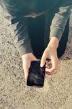 Mujer con un teléfono agrietado quebrado Imagenes de archivo