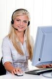 Mujer con un teléfono directo del receptor de cabeza y del ordenador Imagenes de archivo