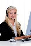 Mujer con un teléfono directo del receptor de cabeza y del ordenador en Imagen de archivo libre de regalías
