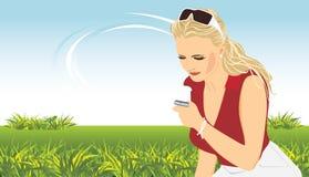 Mujer con un teléfono móvil. Composición del resorte Foto de archivo libre de regalías