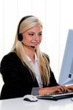 Mujer con un teléfono directo del receptor de cabeza y del ordenador Imagen de archivo