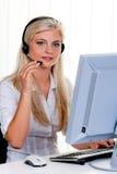 Mujer con un teléfono directo del receptor de cabeza y del ordenador en Imagenes de archivo