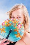 Mujer con un ventilador en un cielo azul del fondo Foto de archivo