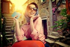 mujer con un viaje de la maleta y boleto en la calle del AIE Imagenes de archivo