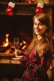 Mujer con un vidrio de champán por la chimenea Mujer joven si Fotos de archivo libres de regalías
