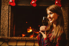 Mujer con un vidrio de vino por la chimenea Wo atractivo joven Foto de archivo