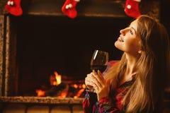 Mujer con un vidrio de vino por la chimenea Wo atractivo joven Imagenes de archivo
