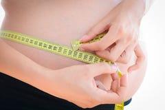 Mujer con un vientre del embarazo que se mide con una cinta métrica Foto de archivo