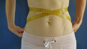 Mujer con un vientre plano Primer en un fondo azul Comida sana, aptitud almacen de metraje de vídeo