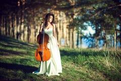 Mujer con un violoncelo en el bosque Fotos de archivo libres de regalías