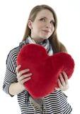 Mujer con una almohadilla del corazón Imagenes de archivo