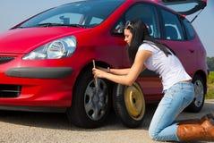 Mujer con una avería del neumático en coche Fotos de archivo libres de regalías