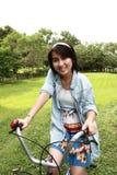 Mujer con una bici al aire libre que sonríe Foto de archivo libre de regalías