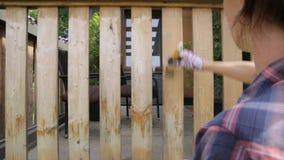 Mujer con una brocha que pinta las verjas de madera de la terraza Tiro al aire libre almacen de metraje de vídeo