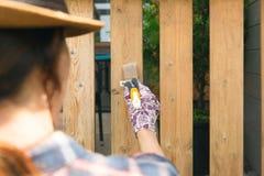Mujer con una brocha que pinta las verjas de madera de la terraza Tiro al aire libre fotos de archivo