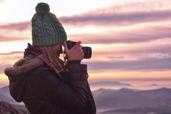 Mujer con una cámara que toma las fotos imagen de archivo libre de regalías