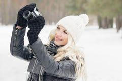Mujer con una cámara vieja en las manos, bosque del invierno Fotografía de archivo libre de regalías