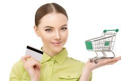 Mujer con una carretilla para los panieres y tarjeta de banco de crédito en h Foto de archivo libre de regalías