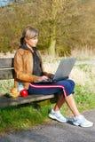 Mujer con una computadora portátil al aire libre foto de archivo libre de regalías