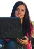 Mujer con una computadora portátil que se sienta en el campo en el cielo Imagen de archivo