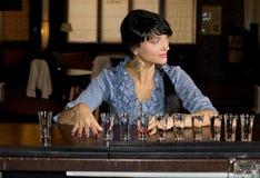 Mujer con una fila de los vasos de medida de la vodka Imagen de archivo