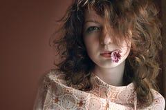 Mujer con una flor en una boca Imagen de archivo libre de regalías