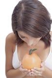 Mujer con una fruta anaranjada Fotos de archivo libres de regalías