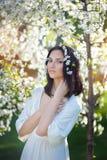 Mujer con una guirnalda de rosas en su cabeza en el jardín florecido imágenes de archivo libres de regalías