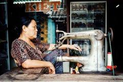 mujer con una máquina de costura delante de sus clientes que esperan de la tienda para imagen de archivo libre de regalías