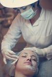 Mujer con una máscara facial en un centro del balneario fotografía de archivo
