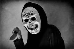 Mujer con una máscara humana del cráneo que sostiene un cuchillo Imagenes de archivo