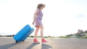 Mujer con una maleta azul almacen de metraje de vídeo
