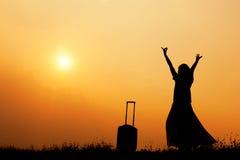 Mujer con una maleta en un prado en la silueta de la puesta del sol Imagenes de archivo