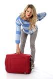 Mujer con una maleta y un dolor de espalda rojos pesados Foto de archivo libre de regalías