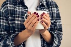 Mujer con una manicura de Borgoña en la camisa de tela escocesa que sostiene la taza blanca Imagenes de archivo