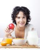 Mujer con una manzana a un desayuno sano en el fondo blanco Imagen de archivo