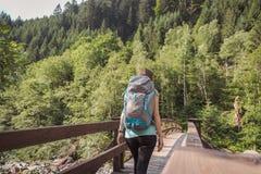 Mujer con una mochila que camina en un puente en el bosque fotografía de archivo libre de regalías