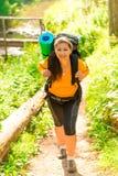 Mujer con una mochila que va para arriba la colina Foto de archivo libre de regalías