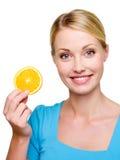 Mujer con una naranja del pedazo Fotografía de archivo