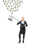 Mujer con una red de pesca que intenta coger el dinero Fotografía de archivo libre de regalías