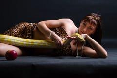 Mujer con una serpiente que sostiene la manzana roja Imagen de archivo