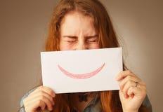 Mujer con una tarjeta de la sonrisa y un x28; emoción, gestures& x29; Imagen de archivo libre de regalías